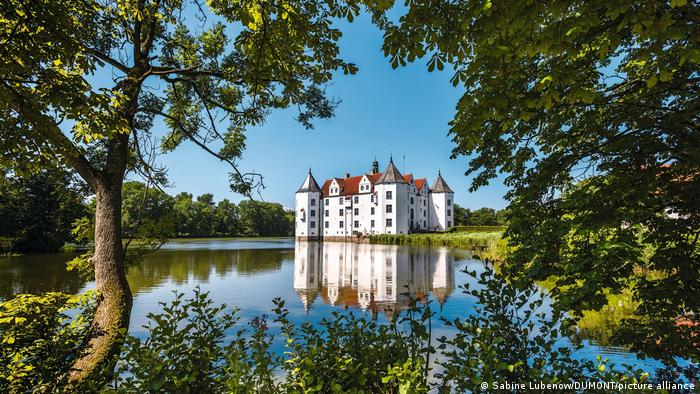 Germany, view through trees and across a lake of Gluecksburg castle