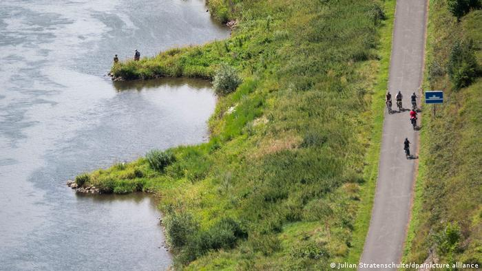 Aerial view of cyclists on the Weser Cycle Route next to the river and its marshes