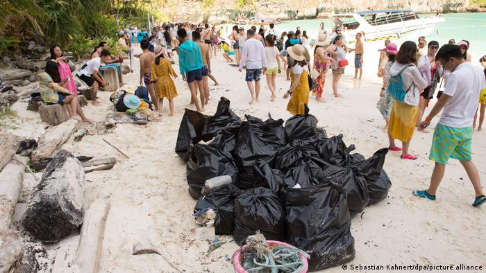 Black bags filled with rubbish on the sand at Maya Bay