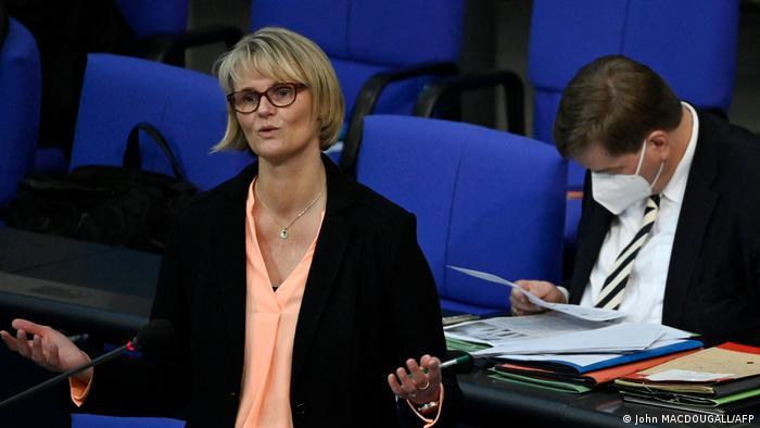 Eine blonde Frau mit Brille im schwarzen Jackett steht im Bundestag vor einem Mikrofon und hebt beim Sprechen ihre Hände mit den Handflächen nach oben. Im Hintergrund sitze ein Mann mit medizinischer Maske und liest in einem Aktenstapel vor ihm