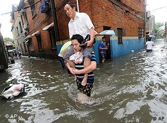 A young man carries an elder person on his shoulder to wade through the waterlogged street, in Nanchang