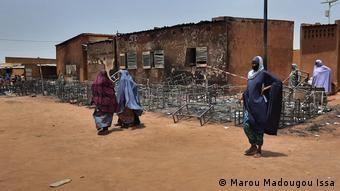 Des femmes devant l'établissement en ruines
