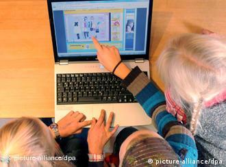 Drei Kinder sitzen vor einem Laptop. Ein Kind zeigt mit dem Finger auf den Bildschirm. (Foto: dpa)