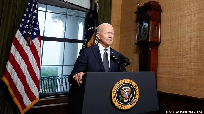 President Joe Biden standing at a pulpit in front of national flag