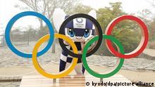 14.04.2021, Hachioji - Das Maskottchen Miraitowa steht 100 Tage vor dem Beginn der Olympischen Spiele hinter den Olympischen Ringen. +++ dpa-Bildfunk +++