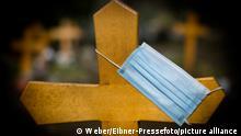 Coronavirus Symbolbild Friedhof Holzkreuz Mundschutzmaske Maske Grabkreuz Tod