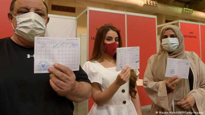 Bahrainis display their COVID-19 vaccine certificates.