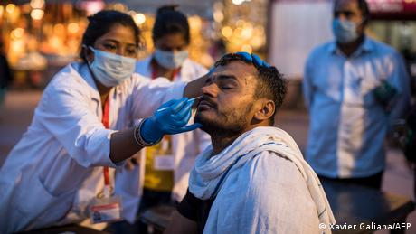 A health worker collects a nasal swab sample from a Hindu devotee