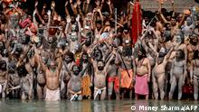 Naga Sadhus (Hindu holy men) take a holy dip in the waters of the Ganges River on the day of Shahi Snan (royal bath) during the ongoing religious Kumbh Mela festival, in Haridwar on April 12, 2021. (Photo by Money SHARMA / AFP)