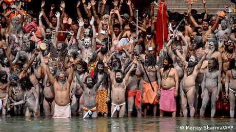 Naga Sadhus (Hindu holy men) take a holy dip in the waters of the Ganges River on the day of Shahi Snan (royal bath) during the ongoing religious Kumbh Mela festival, in Haridwar on April 12, 2021