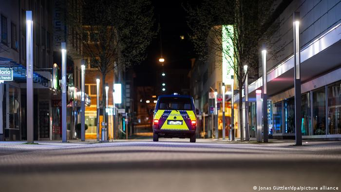 An empty street in Hagen, northwest Germany, with an official vehicle on patrol