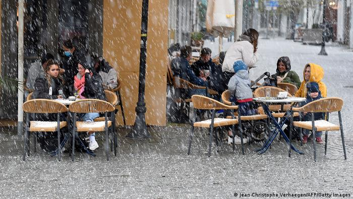 Saarland residents sit outside a cafe.