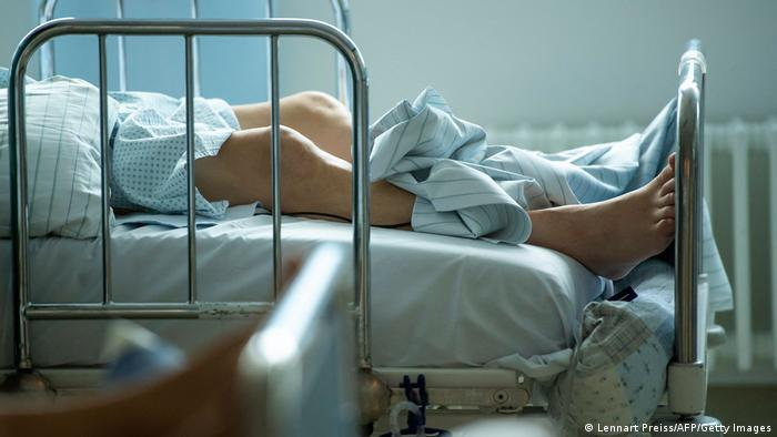 The legs of a hospital patient, lying on a hospital bed