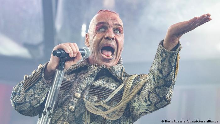 Till Lindemann, singer with microphone, mouth wide open, on stage