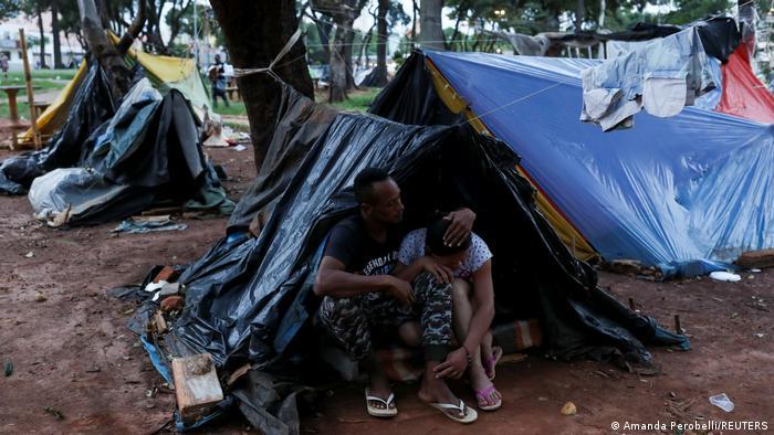Homem e mulher debaixo de barraca improvisada