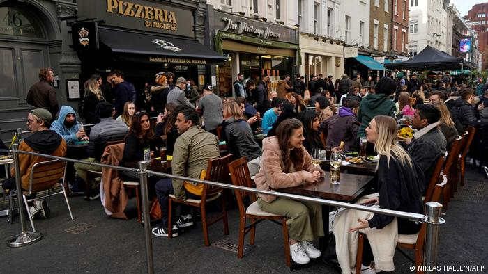 Festive atmosphere on Old Compton Street in London with people dining outdoors
