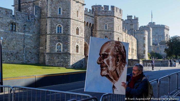 Artist Kaya Mar holds Prince Phillip portrait.