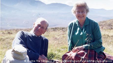 Prinz Philip und Queen Elizabeth II. sitzen lächelnd im Gras.