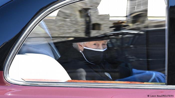 Queen Elizabeth II. sitzt mit Mundschutz im Auto und guckt nach draußen.