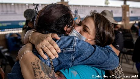 An asylum-seeker hugs another woman at the US border