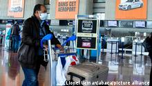 A man wearing a face mask and black leather jacket pushes a trolley at a French airport