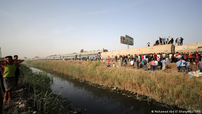 People gather at the site where train carriages derailed, just north of Cairo.