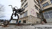 A sculpture in front of a closed down factory housing a self managed community in Sainte-Croix