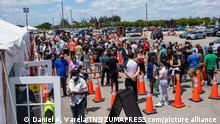 April 14, 2021, Miami, Florida, USA: People line up outside the FEMA operated vaccination site at Miami Dade College - North Campus in Miami, Florida, on Monday, April 5, 2021. The vaccination site has started administering vaccines to all adults regardless of age. (Credit Image: © TNS via ZUMA Wire