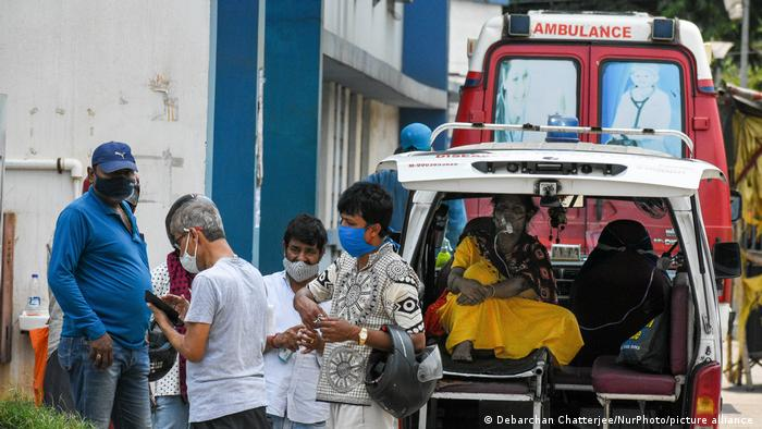 Indian woman waits inside ambulance as her family tries to get her admitted to get treated for COVID-19