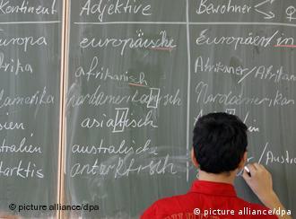 Ein Schüler schreibt deutsche Wörter an die Tafel