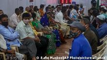 Pessoas de máscara aguardam sentadas em centro de vacinação na Índia