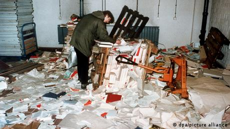 A protester looks through a pile of papers after breaching the Stasi HQ in 1990