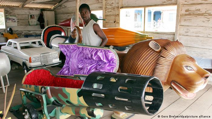 در آفریقا هم فرهنگ ساختن تابوتهای عجیب و غریب و هنری برای مردگان رواج دارد. (عکس: یک تابوتساز غنایی که تابوتهایی به شکل شیر یا برای درگذشتگان نظامی به شکل توپ ساخته است).