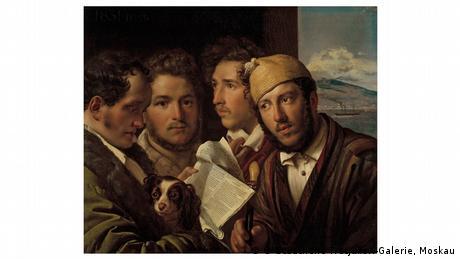 Vier Männer und ein Hund stehen eng beieinander. Einer von ihnen hält eine Zeitung in der Hand und liest daraus vor.
