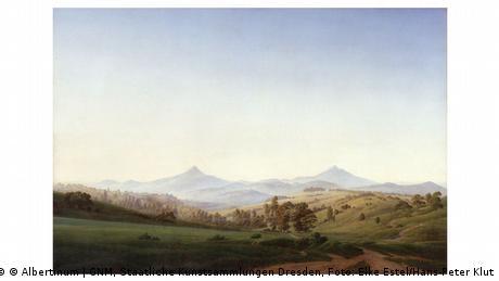 Ein Gemälde von Caspar David Friedrich zeigt eine weite Landschaft mit spitzen Bergen im Hintergrund.