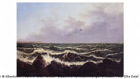 Das Gemälde Brandung auf Rügen gibt den Blick auf aufgewühltes Meer frei. In der Ferne tauchen am Horizont links die berühmten Kreidefelsen der Ostseeinsel auf.