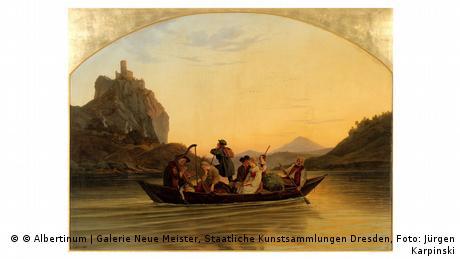 Sechs Menschen rudern auf einem Holzboot über die Elbe. Im Hintergrund taucht im Abendlicht eine Burg auf einem hohen Felsen auf.