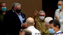 (FILES) In this file photo released by Cuban News Agency ACN taken on October 28, 2020 former Cuban President Raul Castro (C) waves next to Cuban President Miguel Diaz-Canel (L) during the annual session of the Cuban Parliament at the Convention Palace in Havana, amid the new coronavirus pandemic. - Raul Castro, who was for decades in the shadow of his brother Fidel, retires in 2021 at 89 as a pragmatic leader who launched unprecedented economic reforms in Cuba, but who leaves without finishing them and without yielding to the principle of an only party. On the other hand, president and now first secretary of the Communist Party Miguel Diaz-Canel, who was born after the victory of the 1959 revolution, embodies the new generation in power in Cuba, more connected but not necessarily more flexible. (Photo by Ariel LEY / ACN / AFP) / RESTRICTED TO EDITORIAL USE - MANDATORY CREDIT AFP PHOTO / ACN / ARIEL LEY - NO MARKETING NO ADVERTISING CAMPAIGNS -DISTRIBUTED AS A SERVICE TO CLIENTS