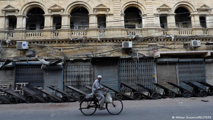 A hawker on a bicycle rides by a closed wholesale cloth market in Lahore