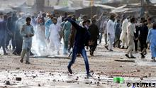 A supporter of the Tehrik-e-Labaik Pakistan (TLP) Islamist political party hurls stones towards police (not in picture) during a protest against the arrest of their leader in Lahore, Pakistan April 13, 2021. REUTERS/Stringer