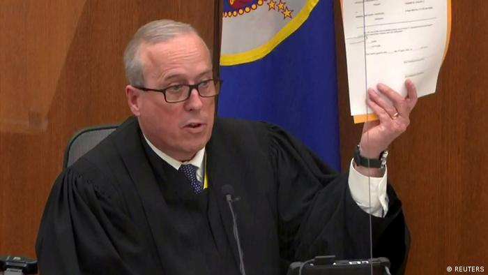 Richter Peter Cahill sitzt im Gerichtssaal und hält ein Schreiben in die Höhe