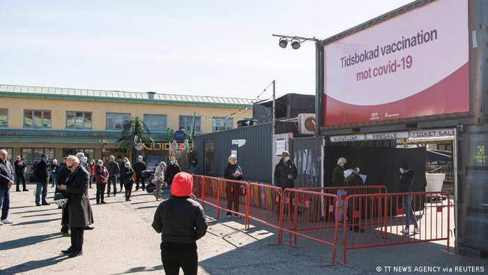 People wait outside a night club turned into a mass vaccination center in Stockholm, Sweden