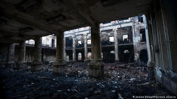 a burnt out building interior with high columns