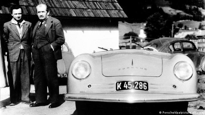 Фердинанд Порше (1875–1951) открива своята фирма в Щутгарт през 1931 година. Делото му по-късно е продължено от неговия син Фери Порше (1909–1998). Тази снимка на двамата е от 1948 година.