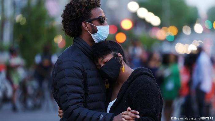 Two people embrace at Black Lives Matter Plaza in Washington, DC
