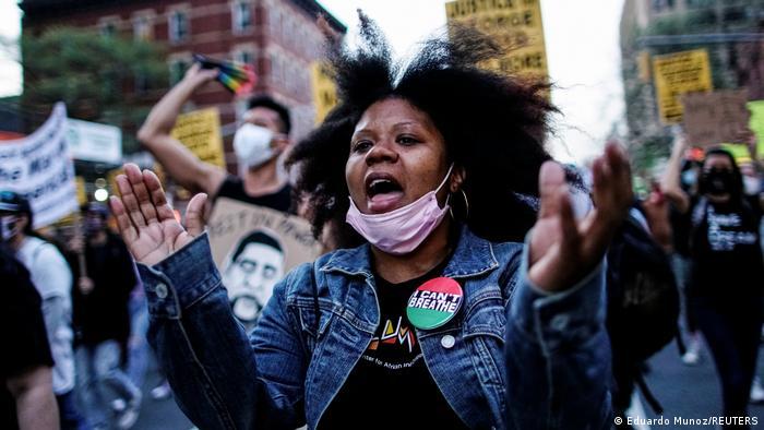 Ein Frau, die einen Button mit der Aufschrift I can't breathe an ihrer Jeans-Jacke trägt, feiert mit anderen in einer Straße New Yorks den Schuldspruch gegen den Ex-Polizisten Derek Chauvin