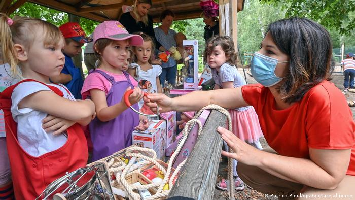 Annalena Baerbock wearing a mask, giving a toy to young children at a daycare outdoors