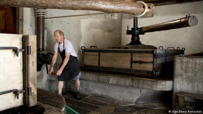 Organic winemaker Jean-Denis Perrochet turns a historic wine press by hand