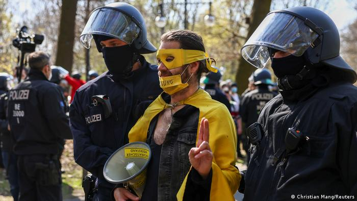 A demonstrator is detained by police in Tiergarten Park, during a protest against the government measures to curb the spread of the coronavirus disease