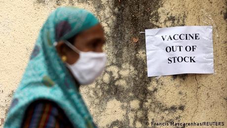 Seorang perempuan di Mumbai membaca pengumuman bahwa vaksin sudah habis